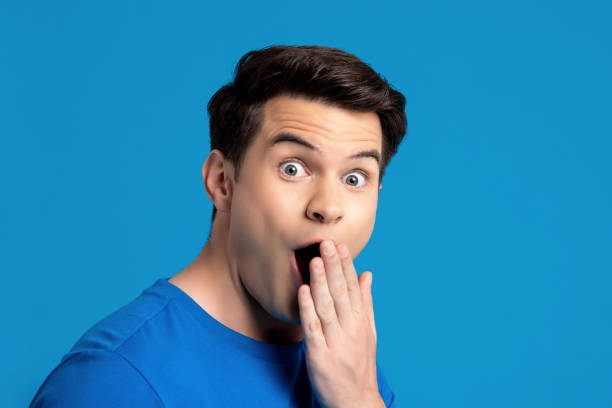 Portrait of caucasian male model in astonished gesture Portrait of  caucasian male model in astonished gesture with hand covering mouth in blue isolated studio background, selective focused gasping stock pictures, royalty-free photos & images