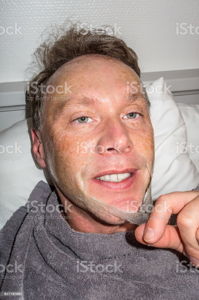 Portrait of Caucasian man removing beauty face mask from his face. royalty-free stock photo