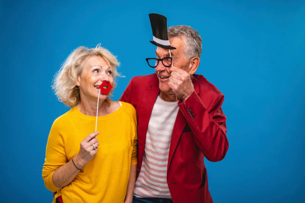 Portrait of Caucasian Seniors Playing with Disguises stock photo