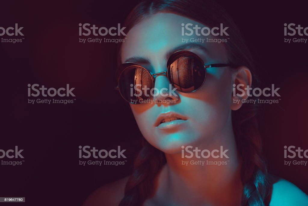 portrait of caucasian young woman with braids in stylish sunglasses stock photo