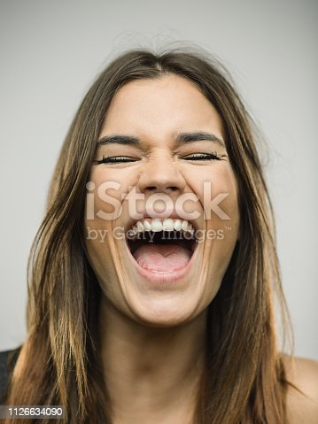 Close up portrait of caucasian young woman with excited expression shouting or singing with eyes closed against white gray background. Vertical shot of spanish real people excited in studio with long brown hair. Photography from a DSLR camera. Sharp focus on eyes.