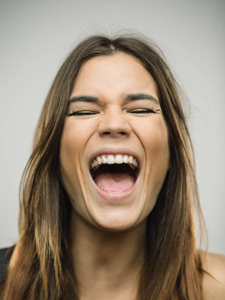 Portrait of caucasian young woman with very excited expression and eyes closed Close up portrait of caucasian young woman with excited expression shouting or singing with eyes closed against white gray background. Vertical shot of spanish real people excited in studio with long brown hair. Photography from a DSLR camera. Sharp focus on eyes. mouth open stock pictures, royalty-free photos & images