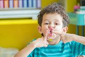 Portrait of Caucasious boy play a fun face in classroom at kindergarten preschool,kid education