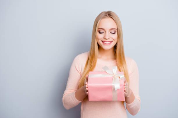 porträt von bezaubernden liebenswert zart sanfte süße süße lovely mit toothy strahlendes lächeln hübsche frau mit langen blonden frisur halten großes paket verpackt in rosa papier isoliert auf grauem hintergrund - jugendliche geburtstag geschenke stock-fotos und bilder