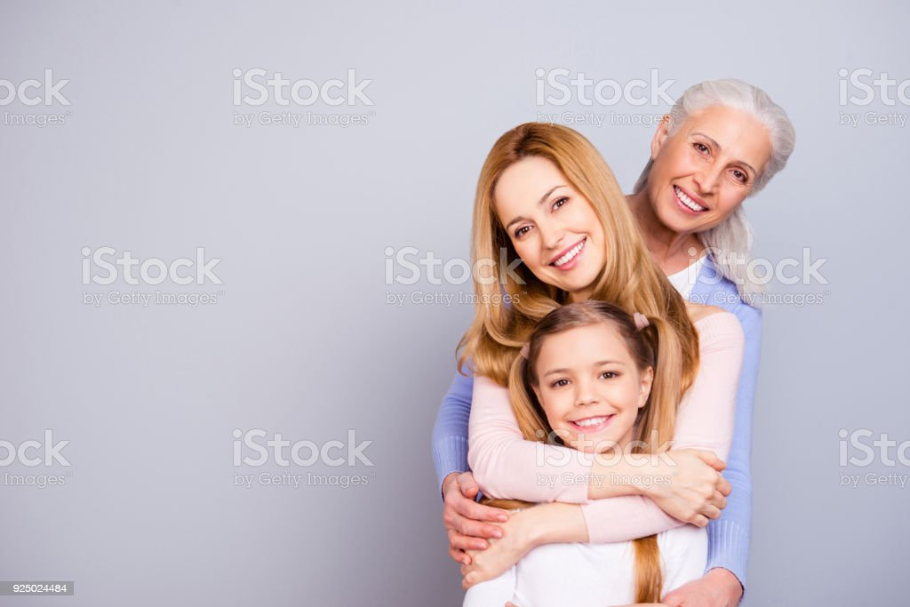 Portrait of charming beautiful friendly king supportive cute family members hugging each other isolated on gray background copyspace stock photo