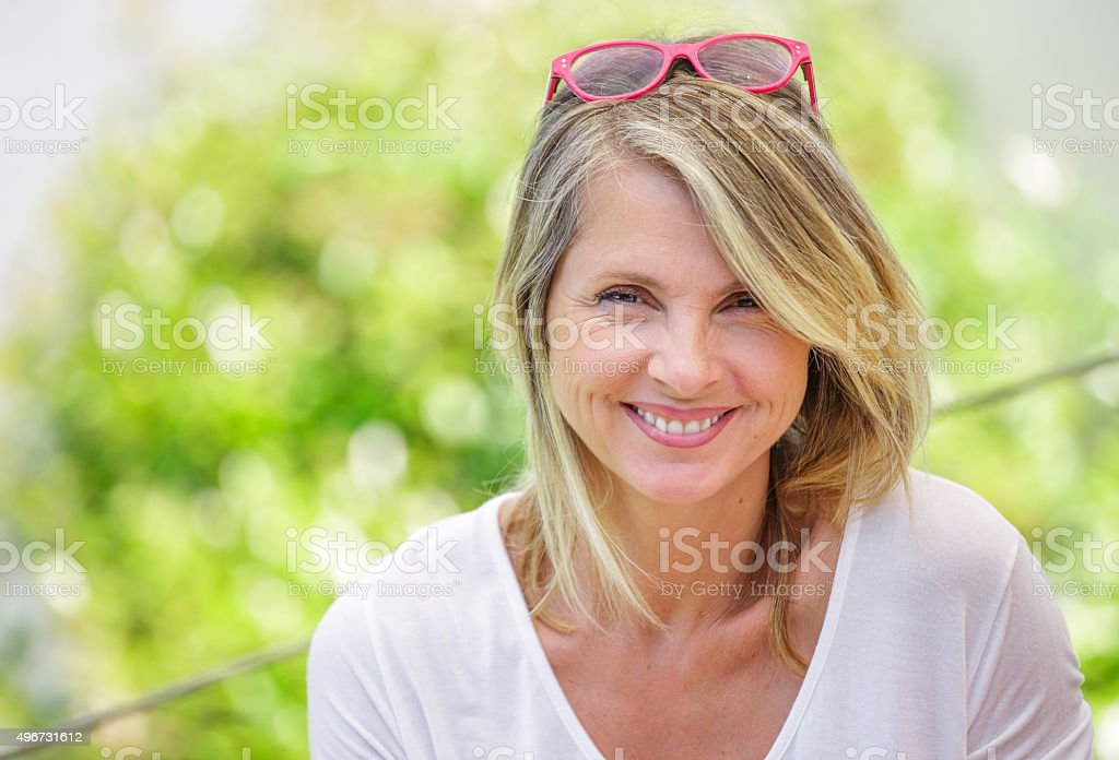 Portrait of charming blond woman of middle-aged smiling in glasses stock photo