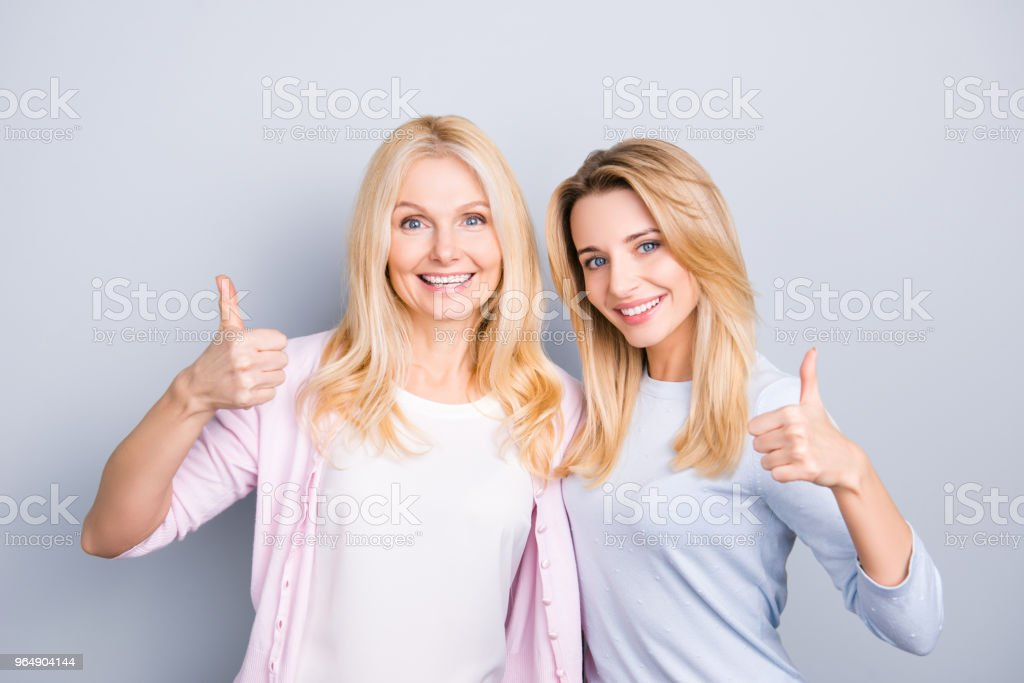 Portrait of charming cheerful hispanic similar mother and daughter with hairstyle beaming smiles gesturing thumbup like symbols isolated on grey background advertisement concept royalty-free stock photo