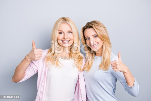 Portrait Of Charming Cheerful Hispanic Similar Mother And Daughter With Hairstyle Beaming Smiles Gesturing Thumbup Like Symbols Isolated On Grey Background Advertisement Concept Stock Photo & More Pictures of Adult