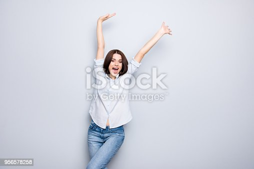 1009493672istockphoto Portrait of charming, crazy, pretty, nice, happy, brunette, caucasian, modern girl with arms up and open mouth, yelling over grey background 956578258