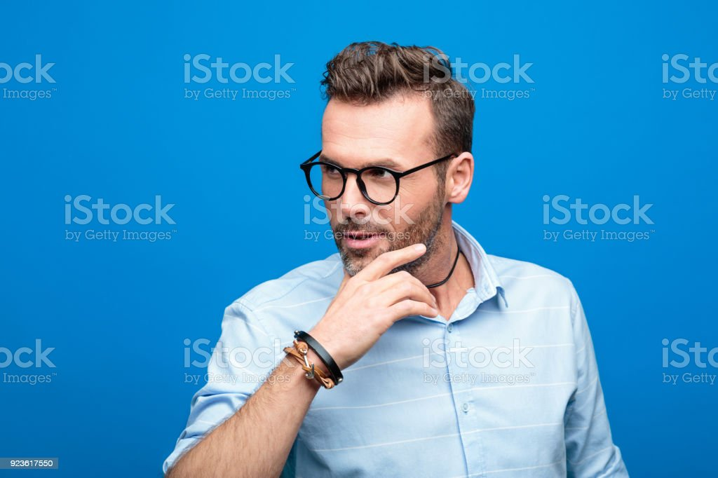 Portrait of charming, handsome man, blue background Summer portrait of charming, handsome man wearing blue shirt and glasses, looking away. Studio shot, blue background. 30-39 Years Stock Photo