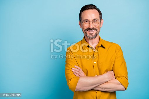 Portrait of charming mature man true boss feel content emotions wear yellow, shirt isolated over blue color background