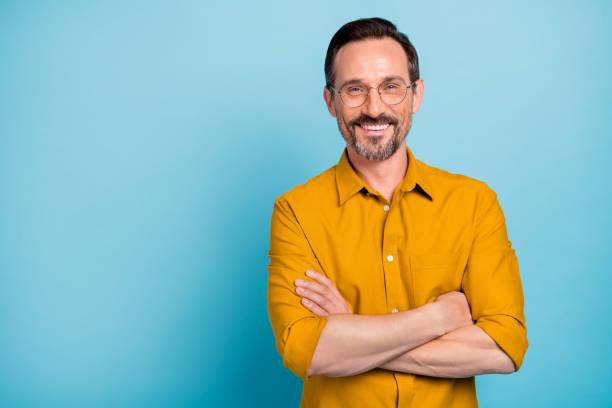 verticale de charme homme mûr vrai patron se sentent émotions de contenu portent la chemise jaune d'isolement au-dessus du fond bleu de couleur - homme photos et images de collection