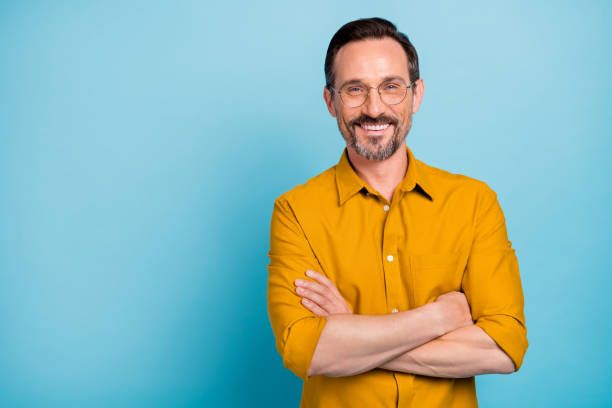 Portrait of charming mature man true boss feel content emotions wear yellow shirt isolated over blue color background Portrait of charming mature man true boss feel content emotions wear yellow, shirt isolated over blue color background background color stock pictures, royalty-free photos & images
