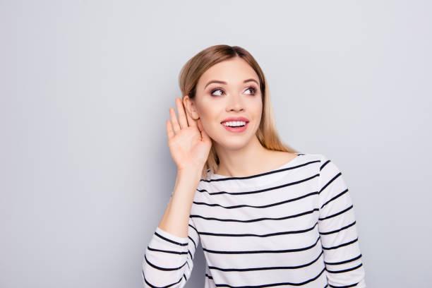 porträtt av charmiga, vackra, foxy, snygga, trendiga, fin, söt flicka i randig tröja med kupad hand nyfiket lyssna på skvaller eller hemlig över grå bakgrund - lyssna bildbanksfoton och bilder