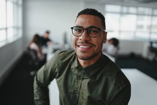 Portrait of charming successful young african american entrepreneur in shirt and eyeglasses looking at camera with smile in office Confident smiling young businessman against coworkers at background hair stubble stock pictures, royalty-free photos & images
