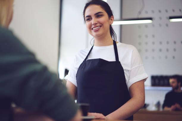 Retrato de la camarera encantadora en buen humor comunicación con el cliente ofreciendo el mejor café bebidas ayuda al cliente para hacer elección, hermosa joven alegre mujer barista listo para tomar pedidos - foto de stock