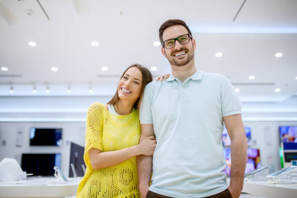 portrait of charming young stylish adorable love couple standing hugged in a tech store. - happy person buy appliances stock photos and pictures