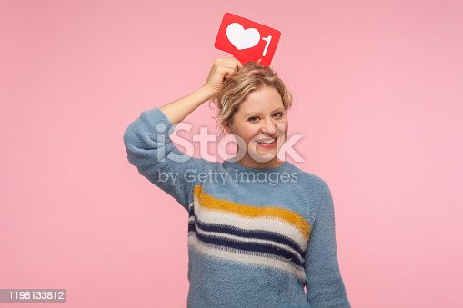 640248524 istock photo Portrait of cheerful adult woman with curly hair in warm sweater holding heart Like icon over head, love content 1198133812