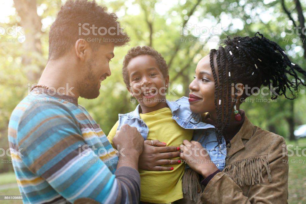 Portrait of cheerful African American parents with daughter in park. royalty-free stock photo