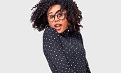 istock Portrait of cheerful African American woman smiling and spinning with her healthy hair, feeling happy, posing over white wall. Beautiful Afro female blowing hair, wearing transparent eyeglasses. 1169347512