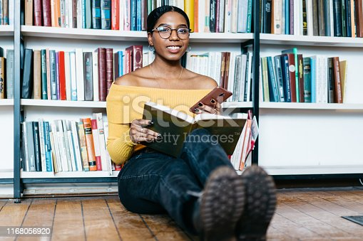 istock Portrait of cheerful african american young woman in casual wear smiling at camera while updating profile on smartphone sitting with book on floor.Dark skinned student spending leisure in library 1168056920