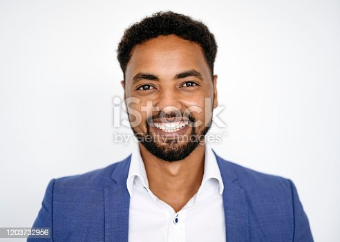 Front view close-up of casual bearded mid adult African businessman wearing blue blazer over open collar shirt and smiling at camera against white background.