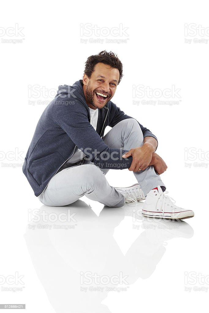 Portrait of cheerful african man sitting on white stock photo