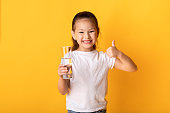 Don't Forget To Drink Water. Cute asian child holding glass of water and showing thumbs up, isolated over yellow wall