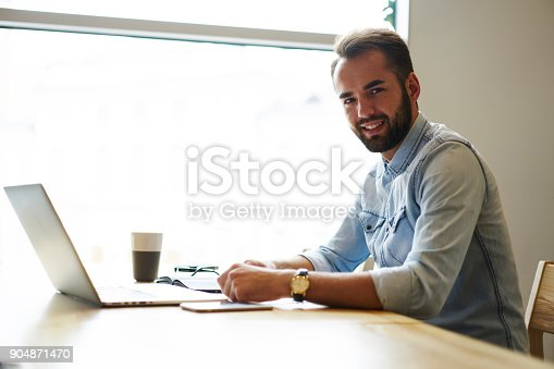 istock Portrait of cheerful bearded graphic designer working remote at modern laptop computer sitting indoors with tasty coffee while looking at camera and smiling.Advertising area for your text message 904871470
