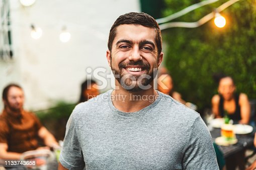 Portrait of cheerful bearded man in yard. Happy male is enjoying garden party with friends in background. He is wearing casuals.