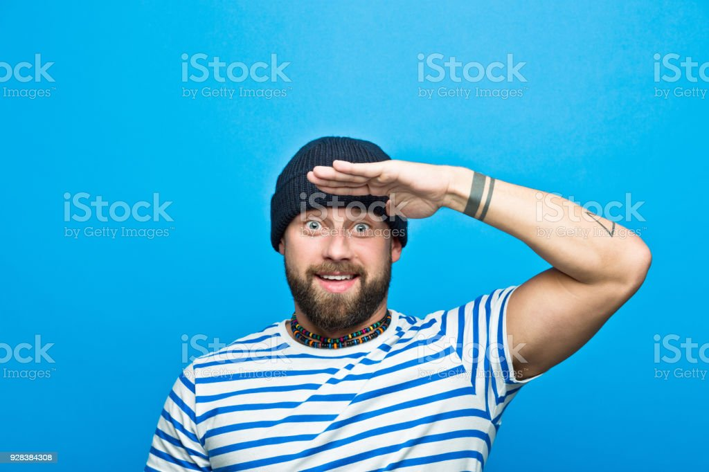 Portrait of cheerful bearded sailor against ble background Portrait of happy, bearded man wearing striped t-shirt and beanie hat saluting. Studio shot, blue background. 30-34 Years Stock Photo