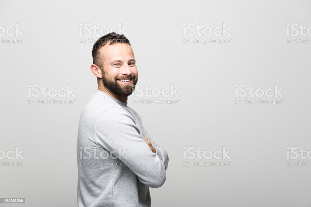 Portrait of cheerful bearded young man smiling at camera, grey background Side view of happy bearded young man smiling at camera. Studio shot, grey background. 30-34 Years Stock Photo