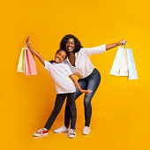 istock Portrait of cheerful black mom and daughter with colourful shopping bags 1191436620