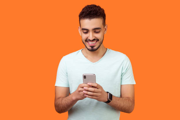 Portrait of cheerful brunette man using cellphone and smiling, reading good news. indoor studio shot isolated on orange background stock photo