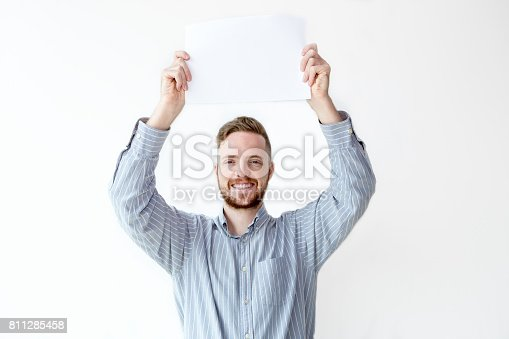 istock Portrait of cheerful businessman holding placard 811285458