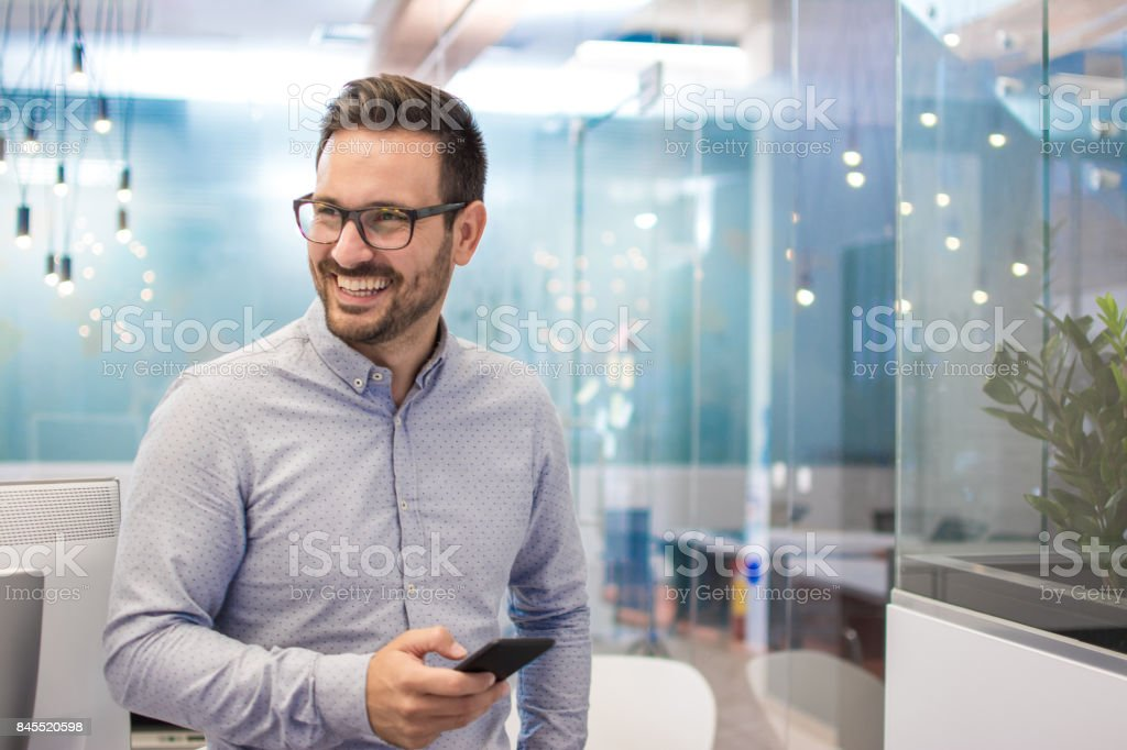 Portrait of cheerful businessman with mobile phone standing in modern office. stock photo