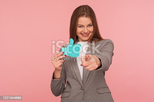640248524 istock photo Portrait of cheerful businesswoman in suit jacket pointing to camera and holding blue thumbs up icon, gesturing hey you 1221344563