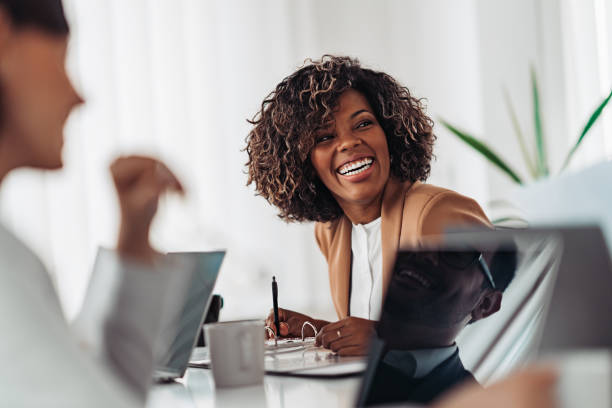Portrait of cheerful businesswoman smiling at the meeting Portrait of cheerful african american businesswoman discussing and smiling at the meeting with colleagues african american ethnicity stock pictures, royalty-free photos & images