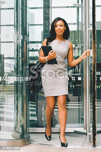 istock Portrait Of Cheerful Businesswoman Walking Through Revolving Doors 518831066