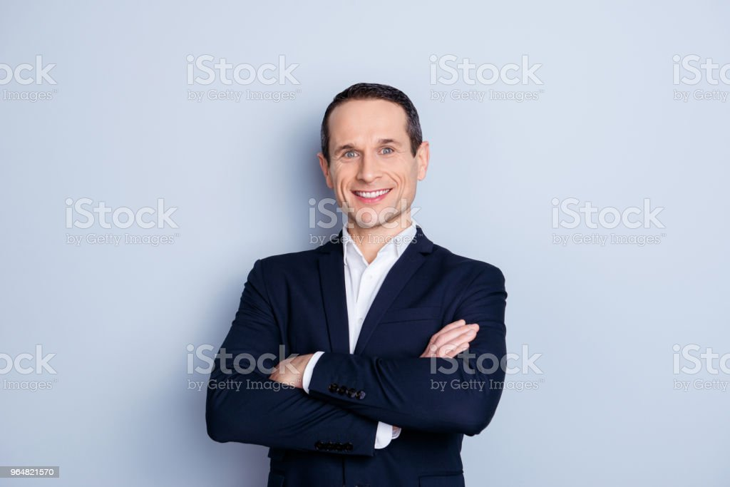 Portrait of cheerful, caucasian, smiling man in formal wear, having his arms crossed, standing over gray background royalty-free stock photo