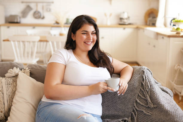 Portrait of cheerful charismatic young overweight female with big breast and long black hair posing in stylish kitchen interior, having coffee on comfortable couch and laughing at funny joke Portrait of cheerful charismatic young overweight female with big breast and long black hair posing in stylish kitchen interior, having coffee on comfortable couch and laughing at funny joke body positive stock pictures, royalty-free photos & images