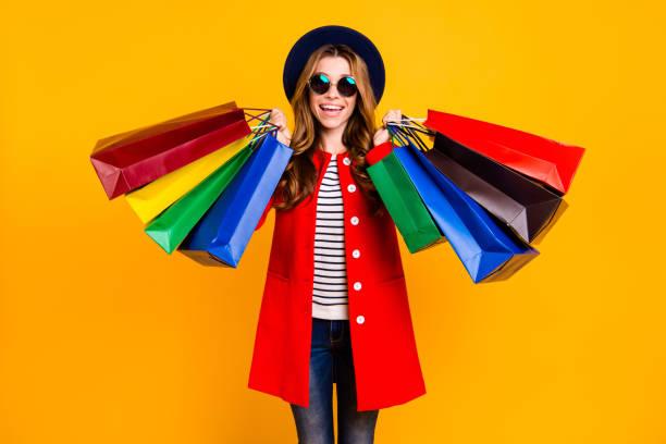 portret van vrolijke vrolijke positieve blij charmante elegante schattig curly-haired dame in brillen brillen houden kleurrijke tassen dragen jeans denim vallen outfit geïsoleerd op gele achtergrond - shopaholic stockfoto's en -beelden