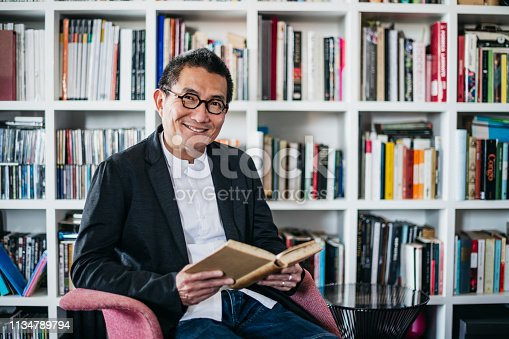 Man in his 50s smiling towards camera, sitting on chair with bookcases in background