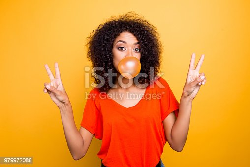 Portrait of cheerful cool girl with modern hairdo blowing chewing bubble gum gesturing v-signs with two hands looking at camera isolated on yellow background