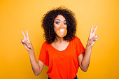 istock Portrait of cheerful cool girl with modern hairdo blowing chewing bubble gum gesturing v-signs with two hands looking at camera isolated on yellow background 979972086