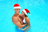 Portrait of beautiful smiling couple in swimming pool with Santa Claus hat. Looking at camera.