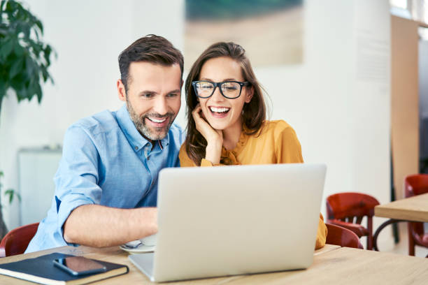 Portrait of cheerful couple using laptop together while sitting in cafe stock photo