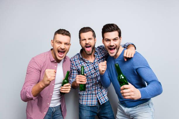 Retrato de alegres, loco, viriles, duros, divertidos chicos con barba y peinado moderno gritando, con botellas con cerveza en mano, aislados en fondo gris, disfrutando de Futbol word - foto de stock