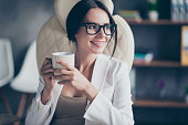 Portrait of cheerful delighted with toothy smile business woman dressed in white jacket is having a pause and holding cup of fresh aromatic latte