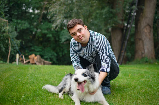 Portrait of cheerful down syndrome adult man playing with dog outdoors in backyard. stock photo